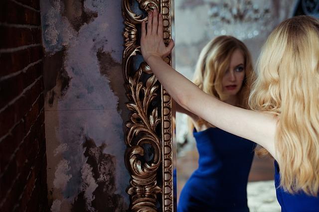 Žena ve společenských šatech, stojící před zrcadlem.jpg