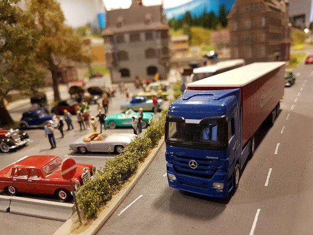 kamion s modrou korbou, maličcí lidi, vyrobeno zřejmě z plastu, městečko