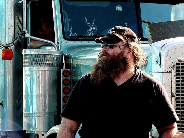 vousatý muž v kšiltovce a brýlích stojící před nákladním automobilem