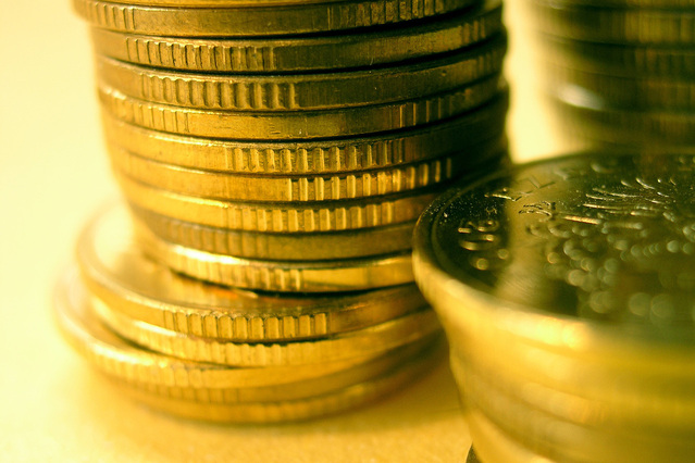 Zlaté mince naskládané na sebe zblízka